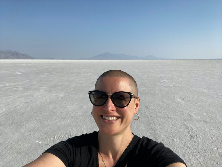 Sarah Dopp, a white woman with a shaved head, is wearing sunglasses, hoop earrings, and a black t-shirt and smiling for a selfie. There is a large empty stretch of salt flats in the background.