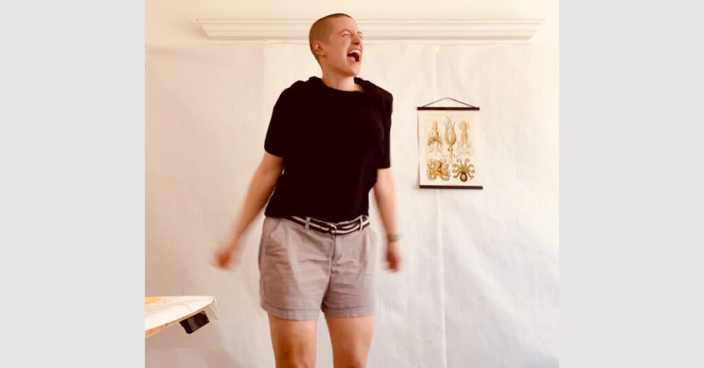 Sarah is caught mid-air while dancing. Her mouth is open in a joyful expression. She is wearing a black t-shirt and khaki shorts.