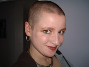 A young woman with a shaved head smiles cheekily at the camera