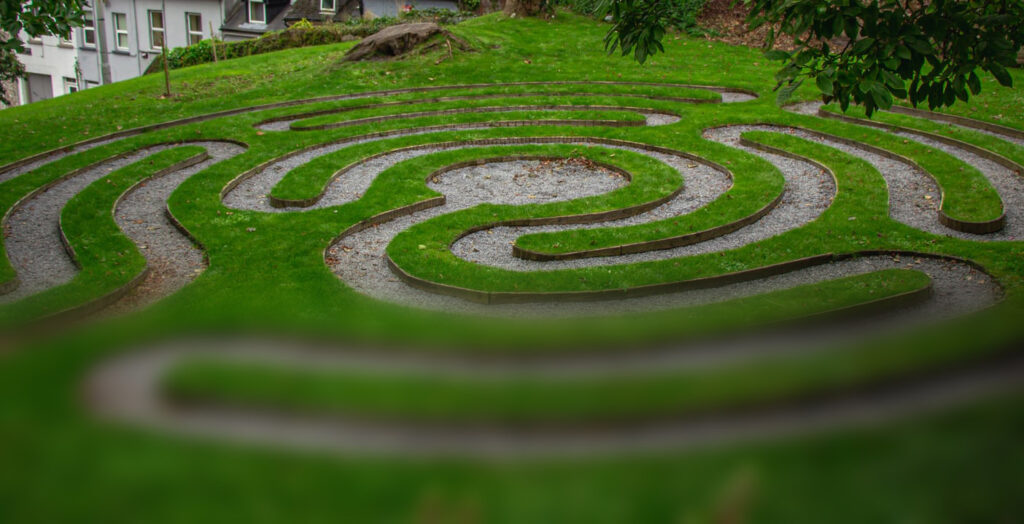 A grassy labyrinth shown in a partially-loaded photo that is clear on the top and blurry at the bottom