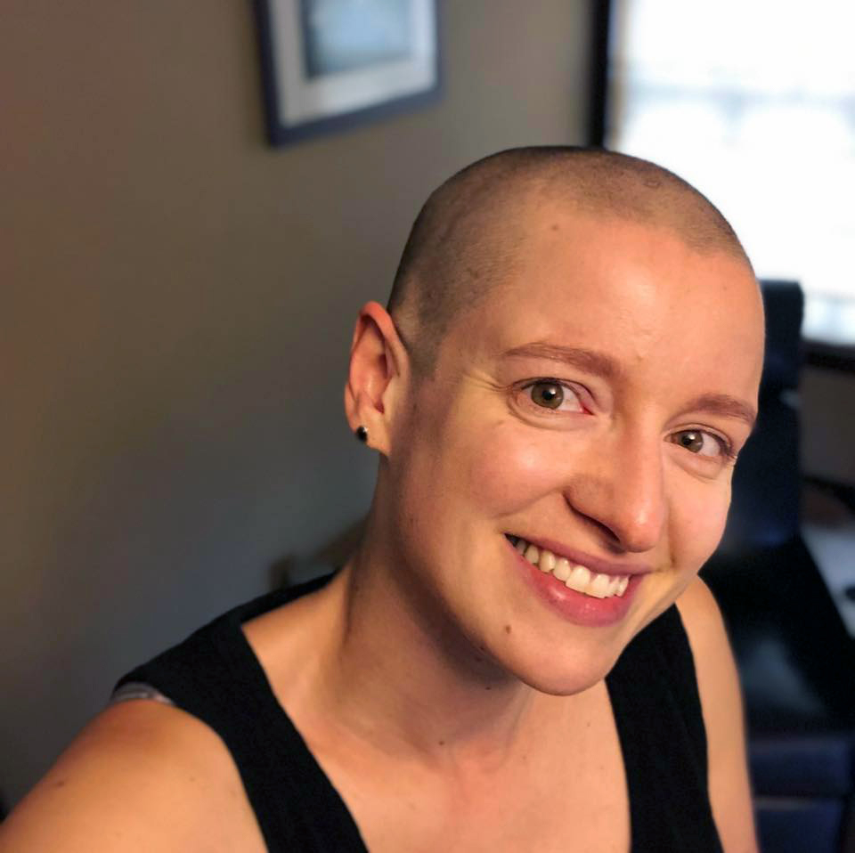 A white woman with a shaved head wearing a black tank top, smiling