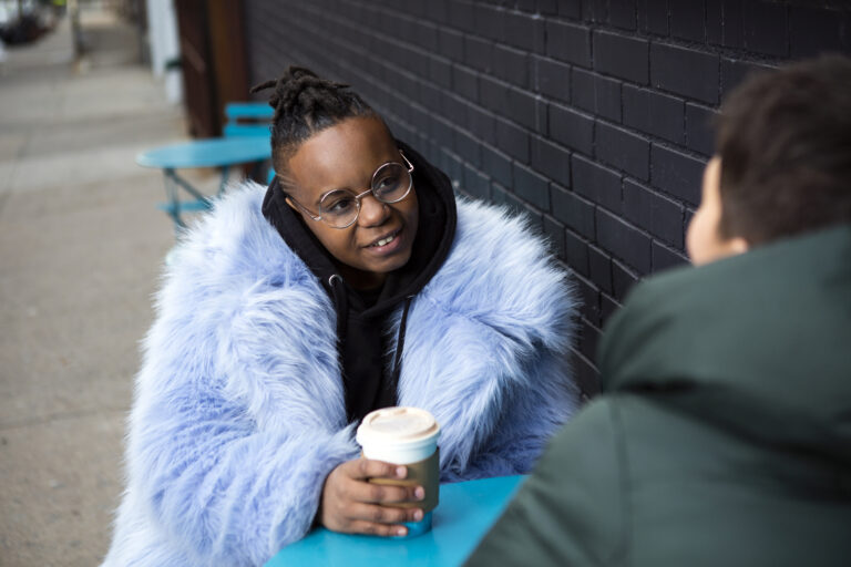 A transmasculine person with a furry blue coat drinking coffee with a friend